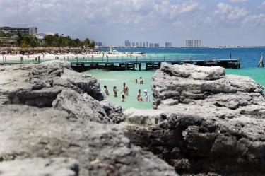 Visitors wade in the water at the beach in Cancun, Mexico.