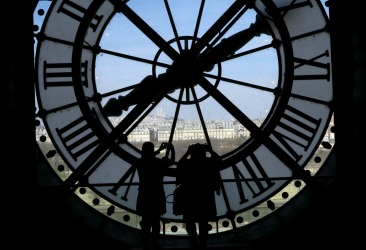 Visitors at the Musee d'Orsay are seen in silhouette as they take pictures from behind a giant clock face at the former Orsay railway station, with a view of the Sacre Coeur Basilica (rear), in Paris. The national museum of the Musee d'Orsay opened in December 1986 and it displays collections of art from the period 1848 to 1914.