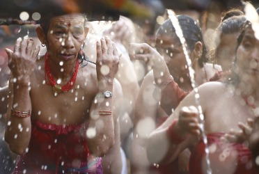 Devotees take a holy bath at the Balaju Baise Dhara (22 water spouts) during the Baishak Asnan festival in Kathmandu. Devotees believe that the water from these stone spouts, which is collected from the catchment area of the Nagarjun forest behind the spouts, will cure pains and skin diseases.