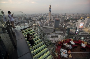 Visitors and tourists enjoy the view from a rooftop bar in central Bangkok.