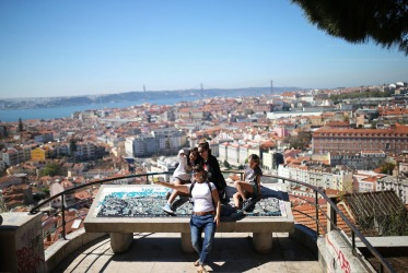 Tourists pose for a selfie at the Nossa Senhora do Monte or 'Our Lady of the Hill' viewpoint overlooking Lisbon, ...