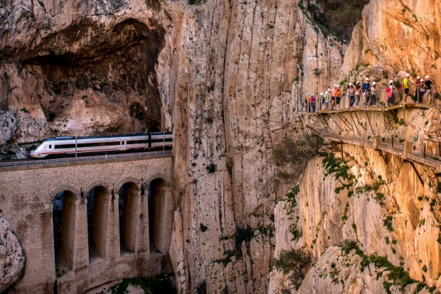 A train passes through a tunnel as tourists walk along the 'El Caminito del Rey' (King's Little Path) footpath in ...