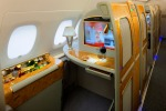 The Emirates A380 superjumbo first class private suite has a stocked mini-bar at your hand, a wood-grain dining table, ...