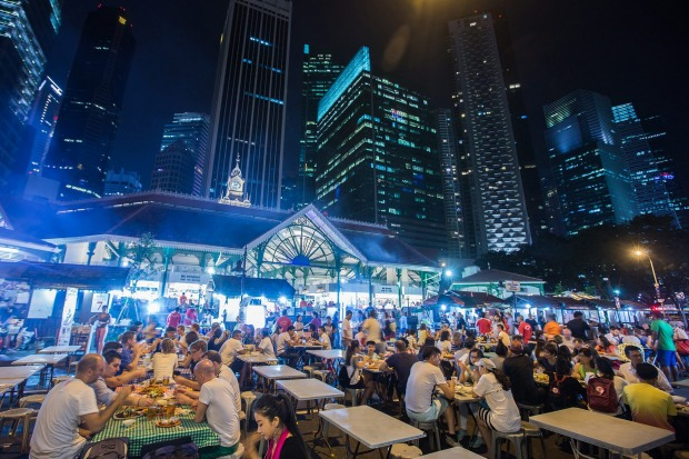 Diners sit at restaurant tables at the Lau Pa Sat food court as commercial buildings stand illuminated at night in the ...