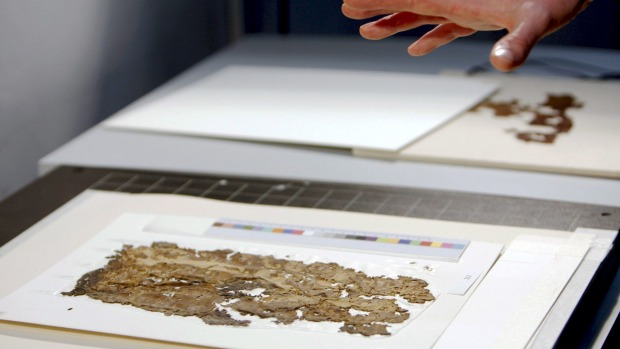 Fragments of Dead Sea scrolls are placed under camera during demonstration in Jerusalem.