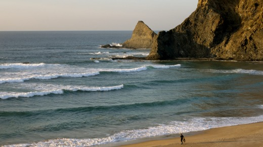 Surfing at Odeceixe beach in the Algarve, Portugal.