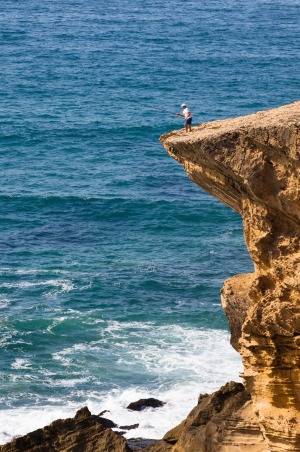 Fisherman on a cliff at Monte Clerigo Beach, Atlantic Coast, Algarve.