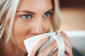 Detail shot of a blue eyed young female drinking coffee