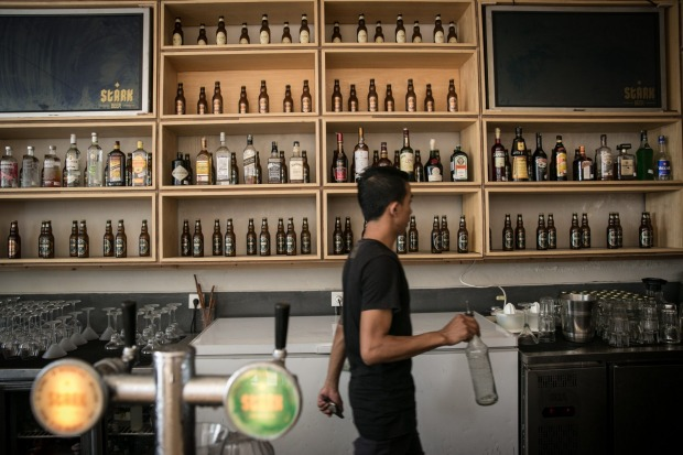 A bartender walks as he prepares a drink in Stark beer house on Legian Street in Kuta, Bali, Indonesia.