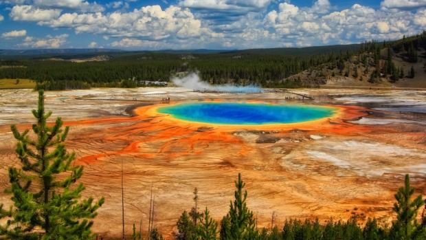 A view of Grand Prismatic Spring with puffy clouds overhead in Yellowstone National Park, Wyoming.