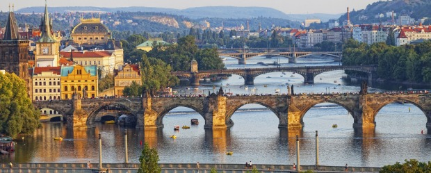 The Vltava River bridges shine in the setting sun.