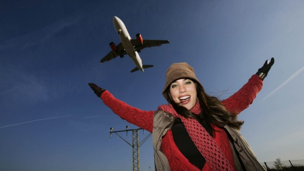 Woman with plane flying overhead.