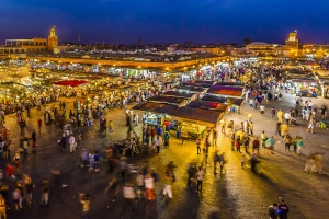 Djemaa El-Fna Marrakesh at night  The rooftop cafes bordering Djemma El-Fna offer a perfect vantage point to take in the square below.  In the evening, just as the theatrics begin, competition is rife: so get there early, enjoy a mint tea (or two) and watch the vendors set up for the evening's trade.  Eventually, wisps of smoke will lace the air, people will multiply, darkness will fall and it will all begin to buzz.