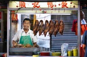 food vendor behind his stall selling  duck, Malaysia.
