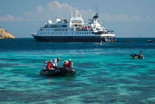 Passengers from Orion approaching Pink Beach over coral reef on Komodo  Island.