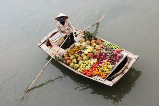 Woman selling fruit from a boat on Halong Bay.