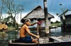 A local enters a village on the Amazon River, Peru in his canoe.