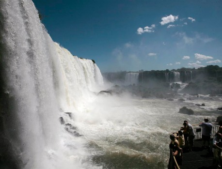Tourists watch the waterfalls from an observation platform at Iguazu National Park in Foz do Iguacu, southern Brazilian