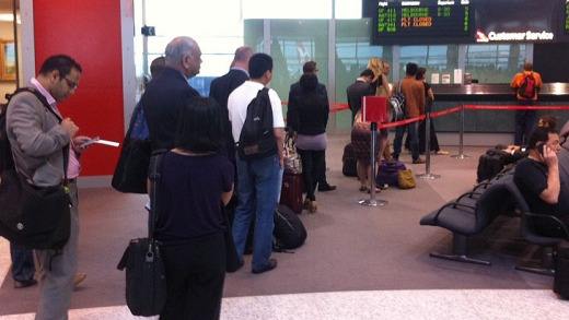 Passengers queue at a crowded service desk where Qantas staff were issuing handwritten boarding passes after a computer ...