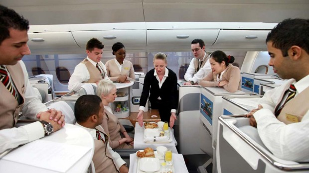 Patricia Walsh, an instructor with Emirates Airline, centre, demonstrates in flight service for business class passengers to a group of economy class cabin crew, during an upgrade course.
