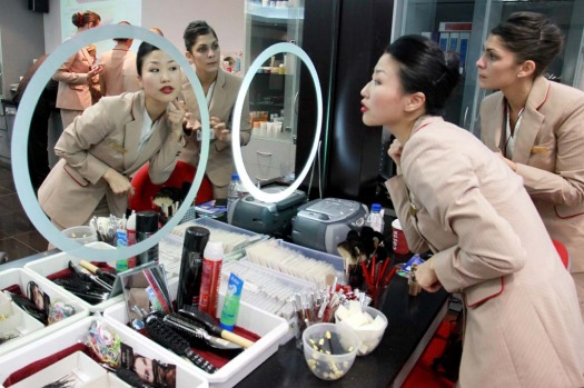 YuJung Kwon, a training instructor for Emirates Airline, left, teaches student Solenne Roussei, right, how to apply her ...