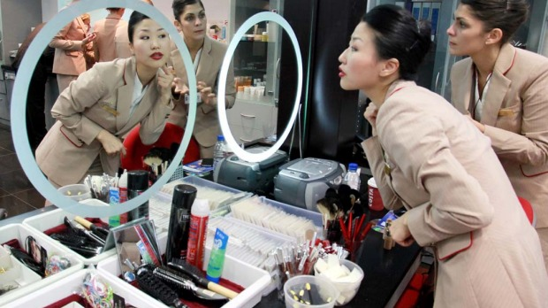 YuJung Kwon, a training instructor for Emirates Airline, left, teaches student Solenne Roussei, right, how to apply her make-up during a training session at the Emirates Aviation College in Dubai.