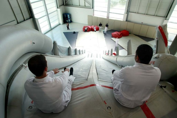 Trainee flight attendants for Emirates practice an emergency exit using escape chutes on an Airbus A380 simulator.