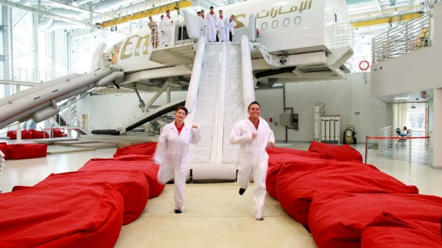 Trainee flight attendants for Emirates practice an emergency exit using escape shoots on an Airbus A380 simulator.