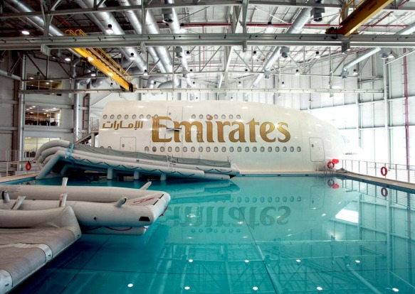Aircraft emergency escape chutes extend into the training pool, next to an Emirates Airline simulator.