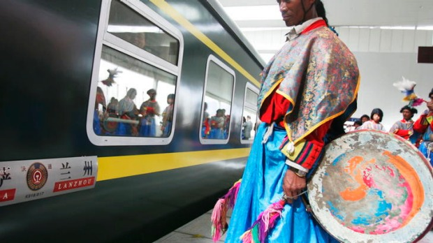 A man in traditional dress waits at the platform.