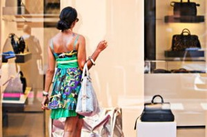 Woman with a smart dress looking in a fashion handbag window  display in Via Monte Napoleone, Milan,