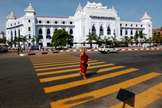 A Buddhist monk crosses the street in front of the City Hall in Yangon. Myanmar's former capital and biggest city Yangon ...