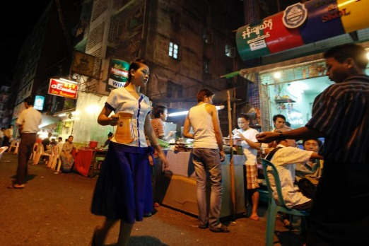 A girl carries a beer jar in Yangon's beer street. Myanmar's former capital and biggest city Yangon is a crumbling ...