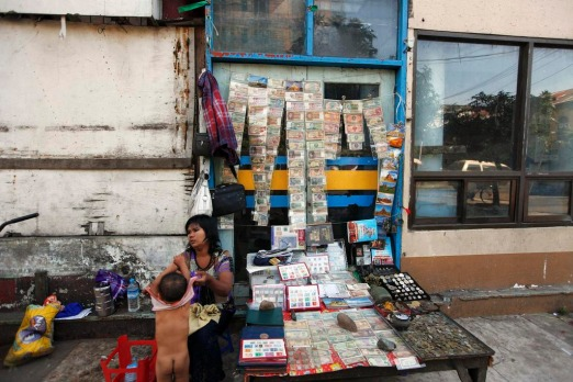 A woman dresses her child as she sells old bank notes in Yangon. Myanmar's former capital and biggest city Yangon is a ...