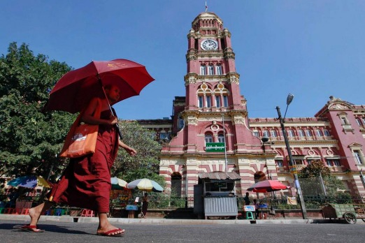 A Buddhist monk walks near the High Court in Yangon . Myanmar's former capital and biggest city Yangon is a crumbling ...