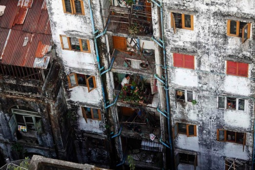 A woman waters flowers on the balcony of her apartment in Yangon. Myanmar's former capital and biggest city Yangon is a ...
