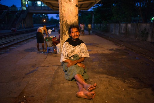 A Burmese man rests at a train station on the outskirts of Yangon. Myanmar's former capital and biggest city Yangon is a ...
