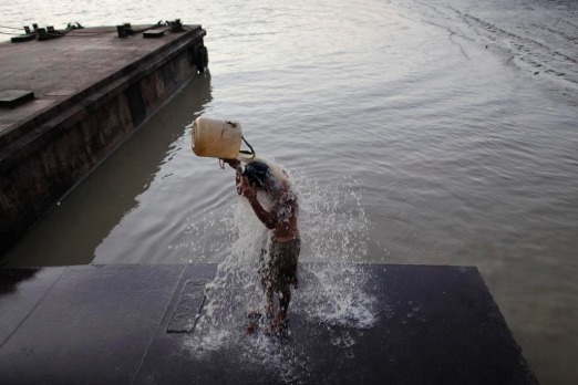 A man washes himself with muddy water from the river at Yangon's river port. Myanmar's former capital and biggest city ...