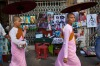 Burmese nuns walk past a street vendor's stall displaying posters of human rights activist Aung San Suu Kyi  in Yangon. ...