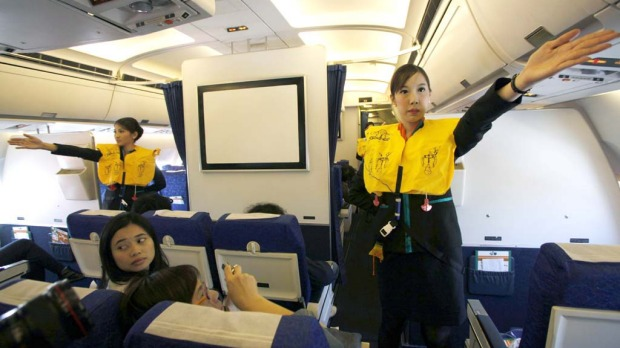 PC Air transsexual flight attendant Chayathisa Nakmai (R), 24, demonstrates in-flight safety to passengers.