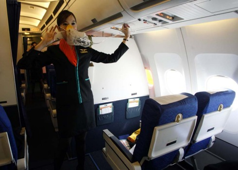 PC Air transsexual flight attendant Chayathisa Nakmai, 24, demonstrates in-flight safety to passengers.