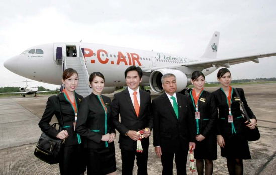 Thai transsexual flight attendants Chayathisa Nakmai, left, Dissanai Chitpraphachin, 2nd left, Nathatai Sukkaset, 2nd right, and Phuntakarn Sringern, right, pose for photograph with PC Air President Peter Chan, 3rd left, and Chairman of PC Air Chawiwat Glamkomol, 3rd right.