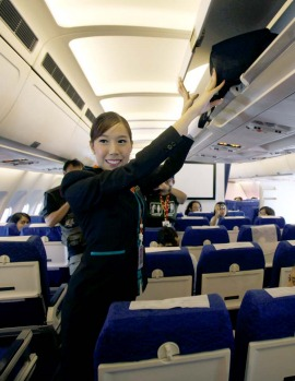 PC Air transsexual flight attendant Chayathisa Nakmai, 24, puts a passenger's luggage in the overhead compartment.