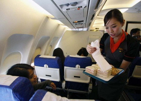 PC Air transsexual flight attendant Chayathisa Nakmai, 24, serves passengers on board the flight.