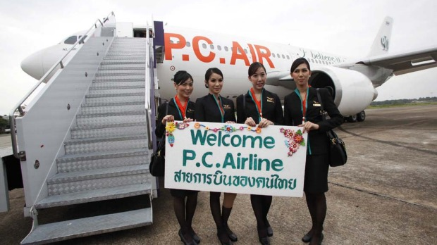 PC Air transsexual flight attendants (L to R):  Nathatai Sukkaset, 26,  Dissanai Chitpraphachin, 24, Chayathisa Nakmai, 24, and, Phuntakarn Sringern, 24, pose for photographers in front of a PC Air plane at Surat Thani Airport.