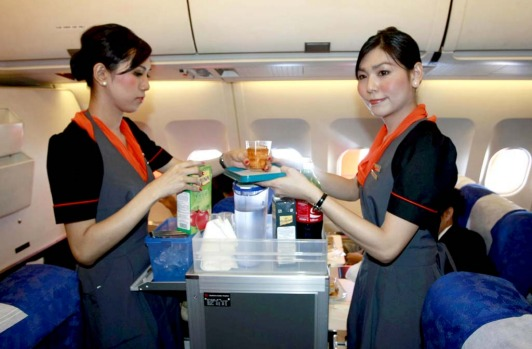 Thai transsexuals flight attendants Nathatai Sukkaset, right, and Phuntakarn Sringern serve soft drinks on board the plane.