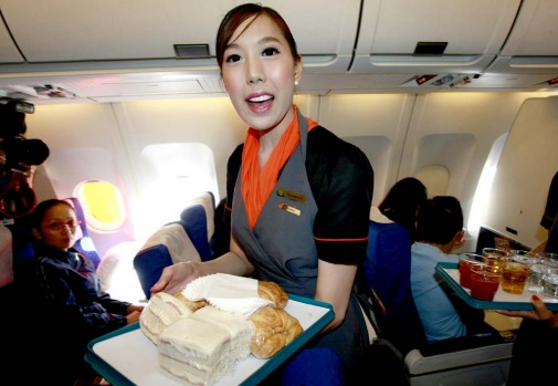 Thai transsexual flight attendant Phuntakarn Sringern serves food during the flight.