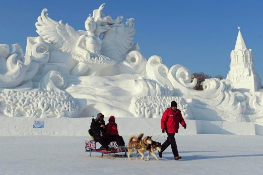 An employee pulls a dog sled carrying tourists in front of a snow sculpture ahead of the 13th Harbin Ice and Snow World ...