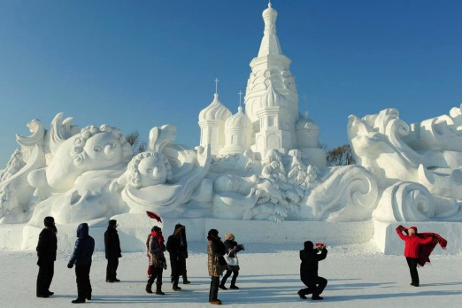 Tourists take pictures in front of a snow sculpture ahead of the 13th Harbin Ice and Snow World in Harbin, Heilongjiang ...