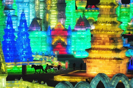 A horse carriage carrying tourists travels past ice sculptures during the lights testing period of the 13th Harbin Ice ...